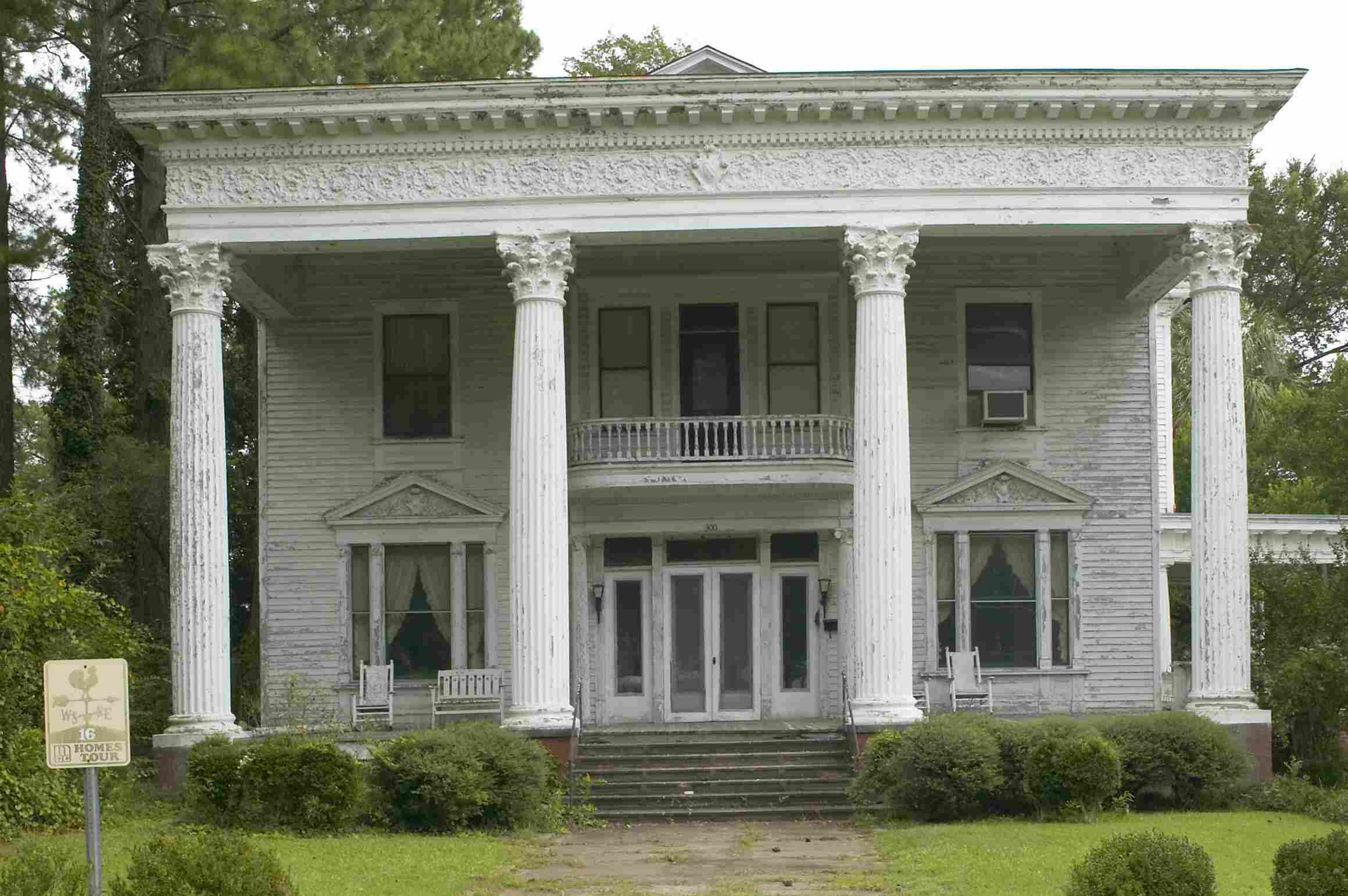 flat-roofed mansion with imposing classical facade, including large, two-story tall columns and an ornate horzontal band between the column capitals and the dentils under the roof eave