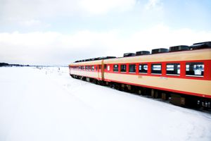 A red Japanese passenger train runs on a railway covered with snow