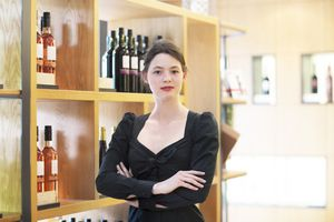 Business owner in wine shop arms crossed looking at camera