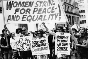 Women hold up protest signs, with the largest sign reading,