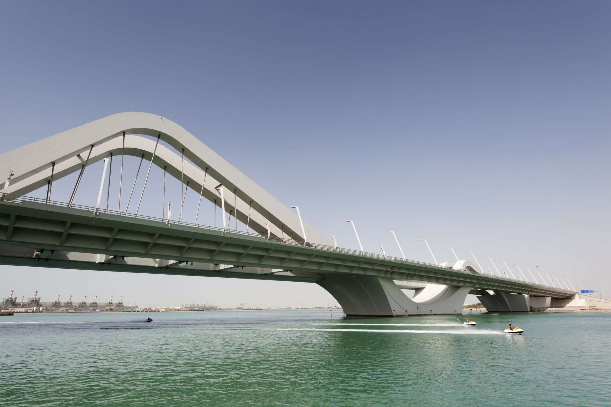 Highway bridge with cantilevered road decks suspended from symmetrical steel arches