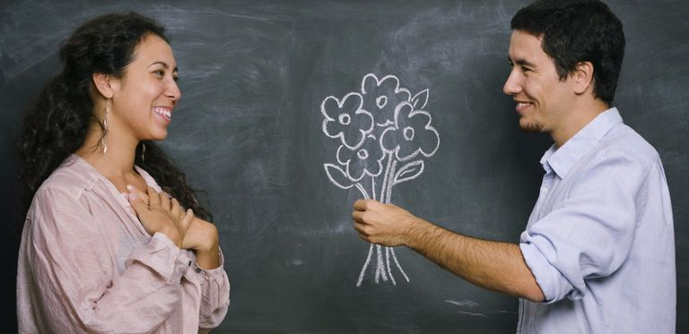 Man giving woman flowers on chalkboard