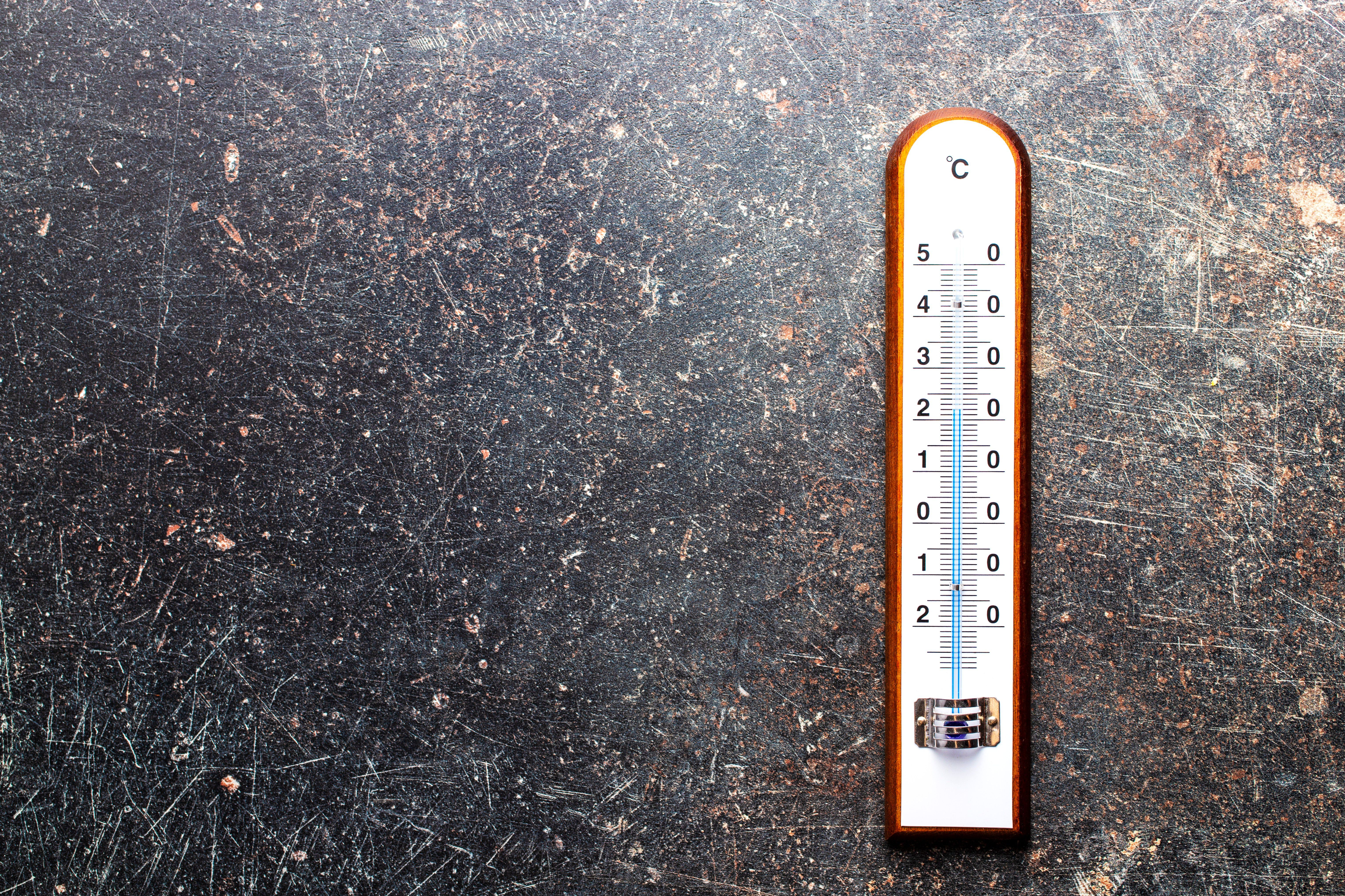 A wooden thermometer lying on a dark surface