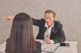 Angry Male Manager Shouting On Female Colleague In Office