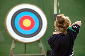 Rear view of girl aiming at target with bow and arrow.