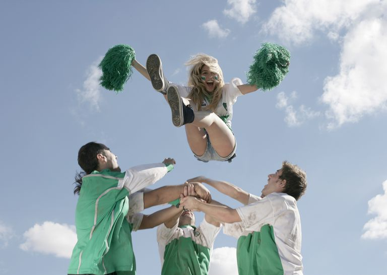 Football players throwing cheerleader in air