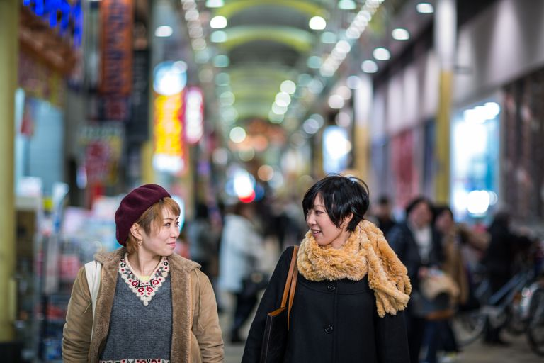 2 young women walking and talking while shopping