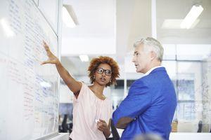 Businesswoman explaining strategy on whiteboard