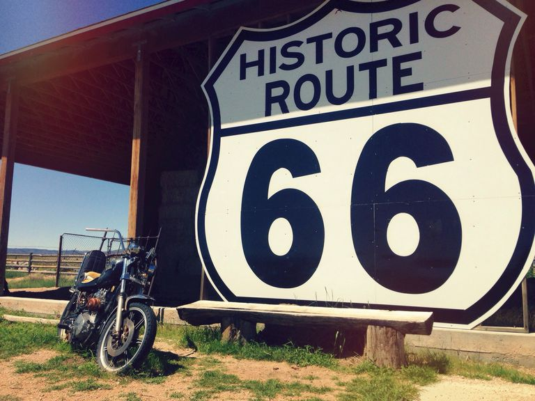 "Motorcycle next to a building with a large ""Route 66"" sign"