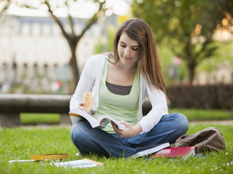 Student sitting in grass studying