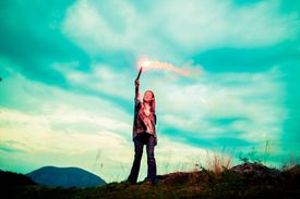 Woman waving a torch above her head.