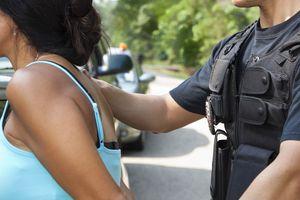 Policía deteniendo a mujer hispana.