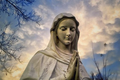 Low Angle View Of Virgin Mary Statue Against Cloudy Sky