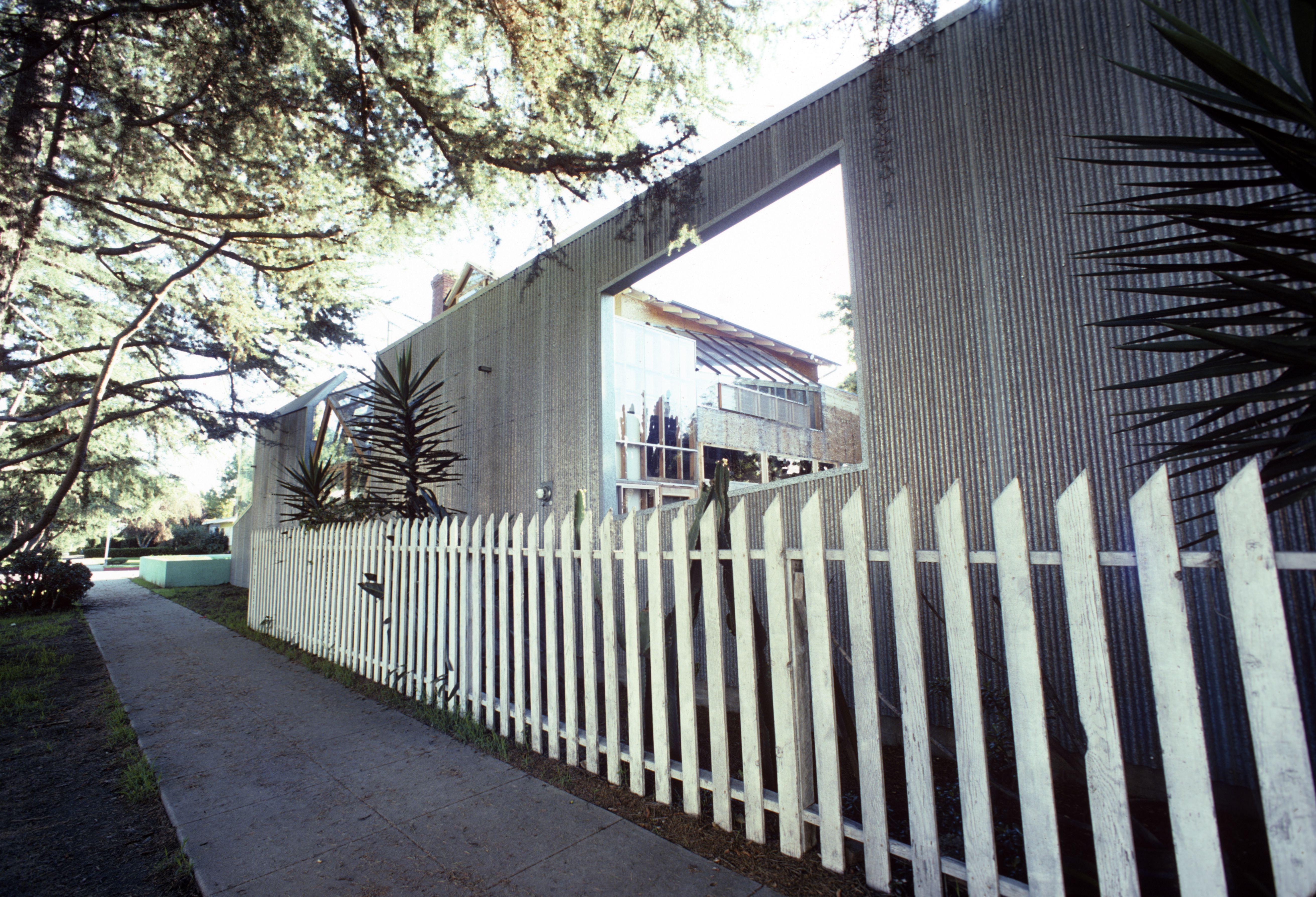 Exterior of Gehry's home shows picket fence in front of modernist detached curtain facade, 1980