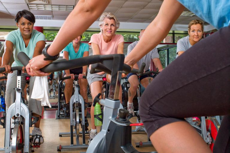 988235d32 Female trainer with group on exercise bikes