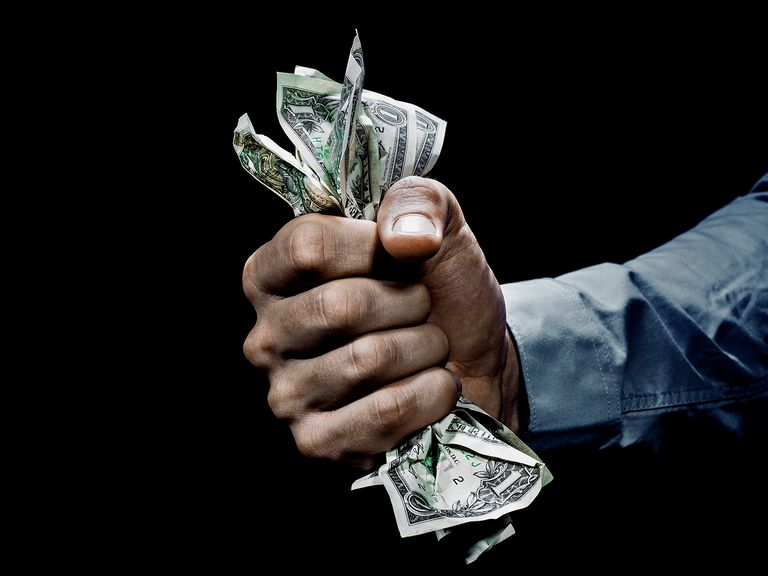 Hand holding money hard