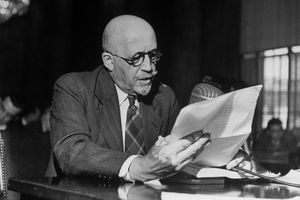 W. E. B. DuBois wearing glasses, seated at a table, looking at paperwork