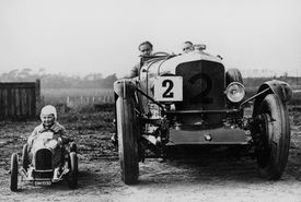 A child in a toy car alongside Frank Clement and Woolf Barnato in a Bentley Speed 6 racing car (1930)