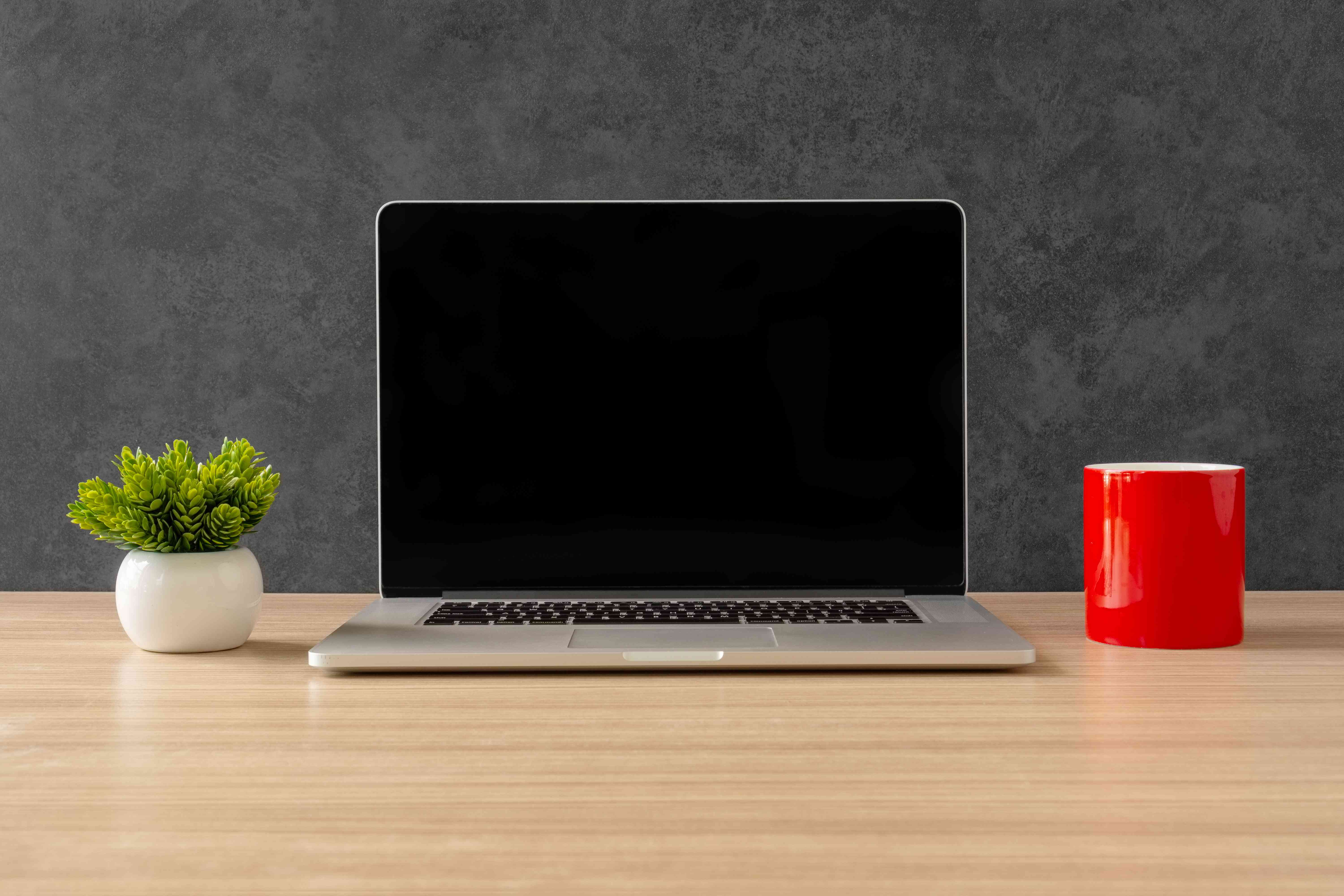 Laptop and Red Coffee Mug on Office Desk