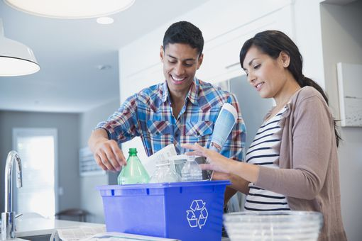 Happy couple recycling plastic bottles and papers at home