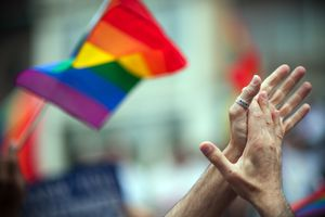 a couple touches hands in front of a rainbow flag