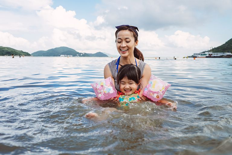 Mom teaching toddler to swim in the sea