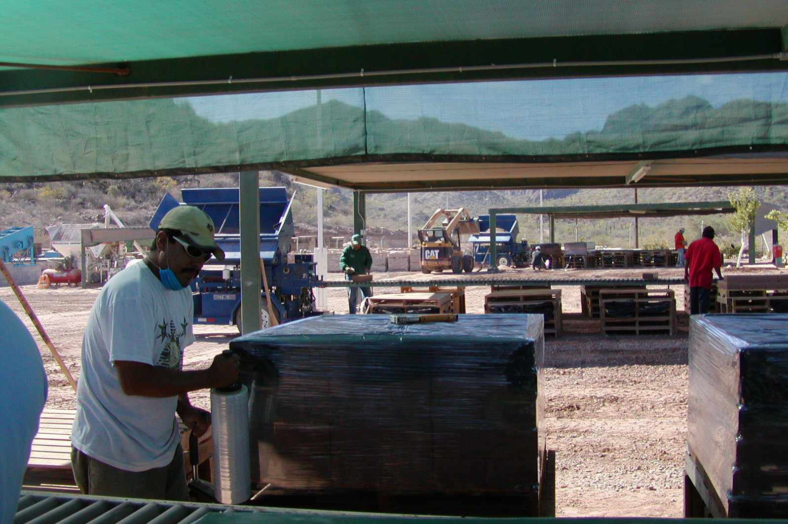 man in white t-shirt using plastic wrap to cover a pallet of blocks at a compression station under a tent-like cover