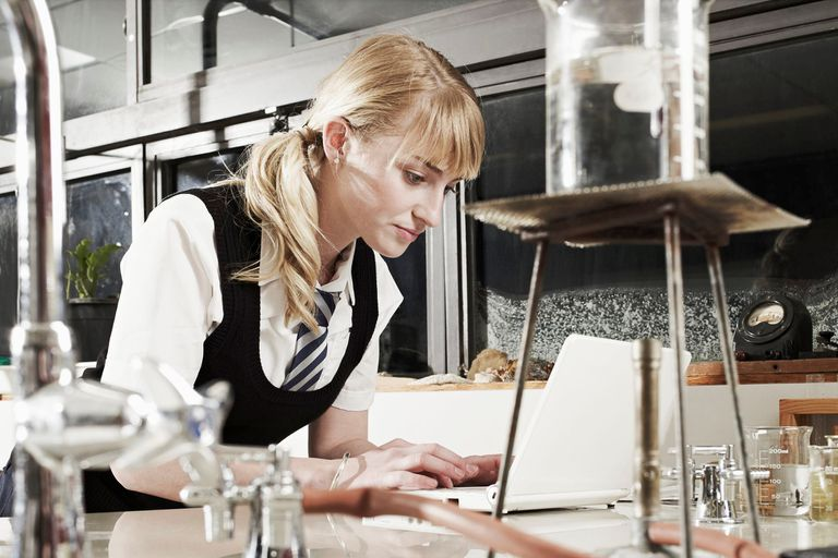 A young woman in a school uniform typing on a laptop in a laboratory