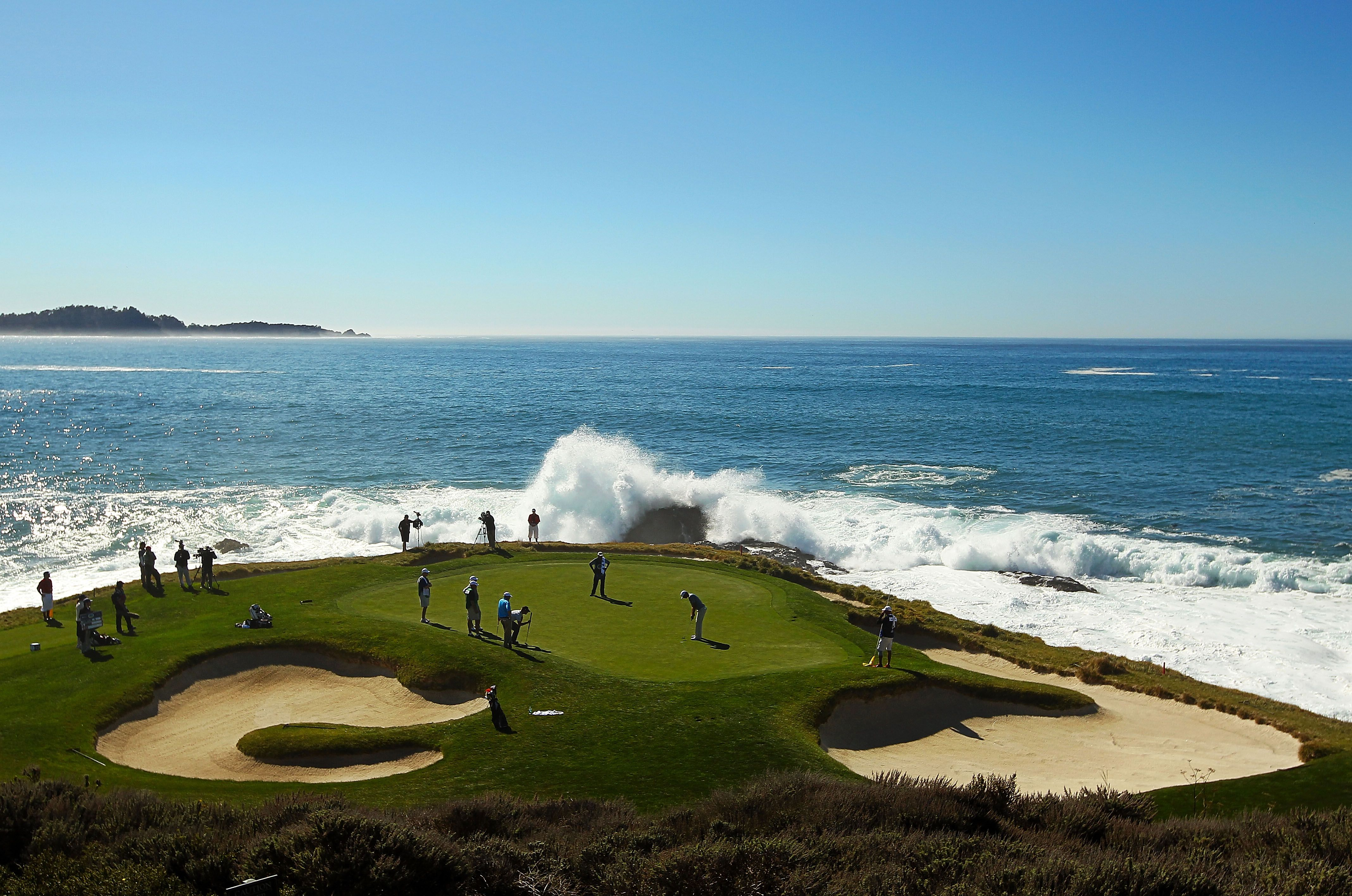 Golfers On The 7th Green At Pebble Beach As Waves Crash Behind