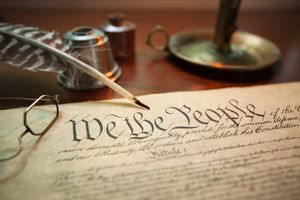 The Preamble to the U.S. Constitution with a feather quill, candle holder, etc.