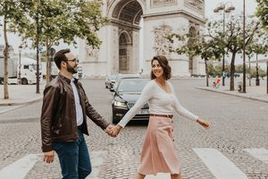 Woman and man walking across the street in front of the Arc de Triomphe in Paris.
