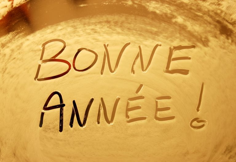 Happy new year in French written in shaving foam on a mirror.