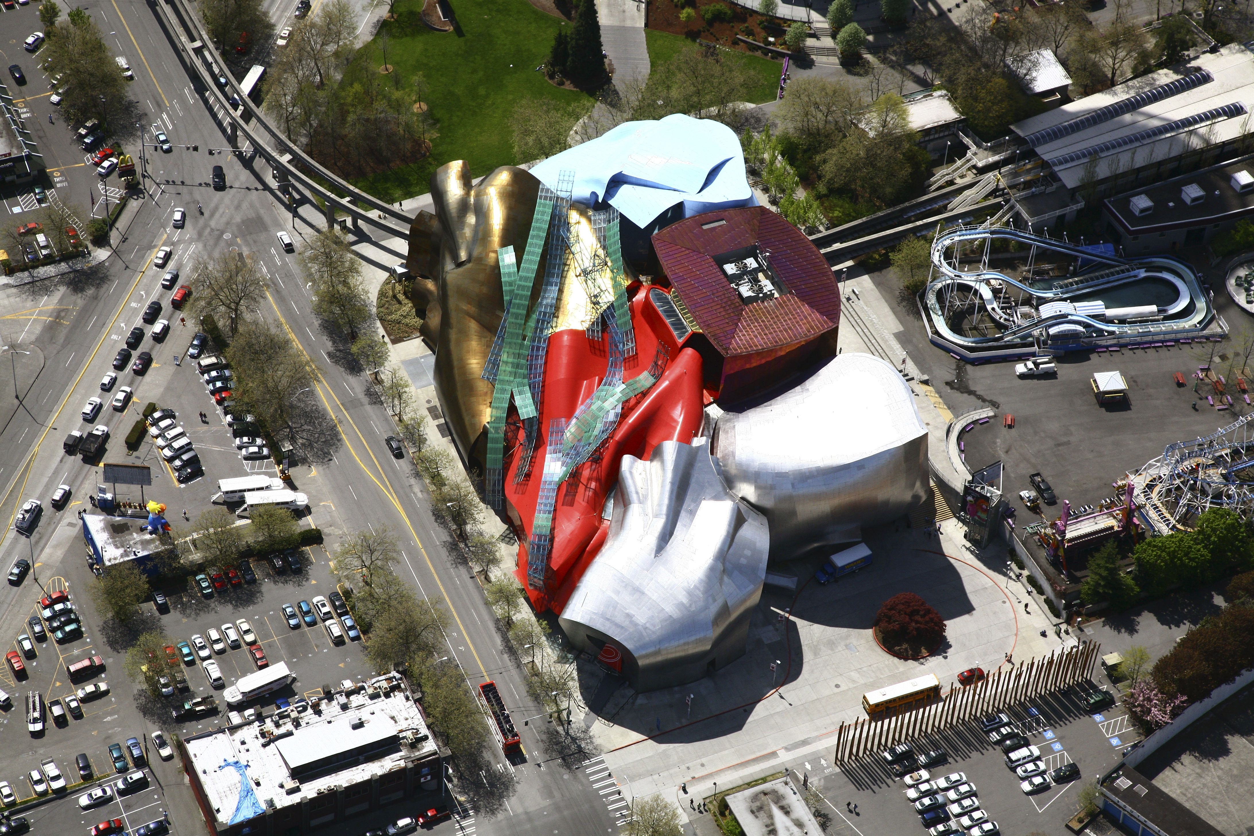 Aerial view of a music museum looks like a trash heap from above with a train running through it