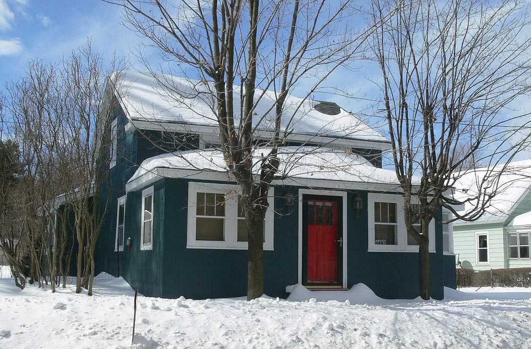 Una puerta roja brillante es una característica tradicional en muchas casas.  Esta casa de campo está pintada de un rico tono de gris, casi negro.