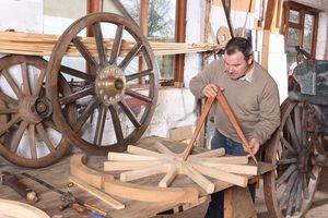 A wheelwright building a wagon wheel
