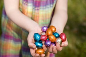 Girl holding many chocolate Easter Eggs