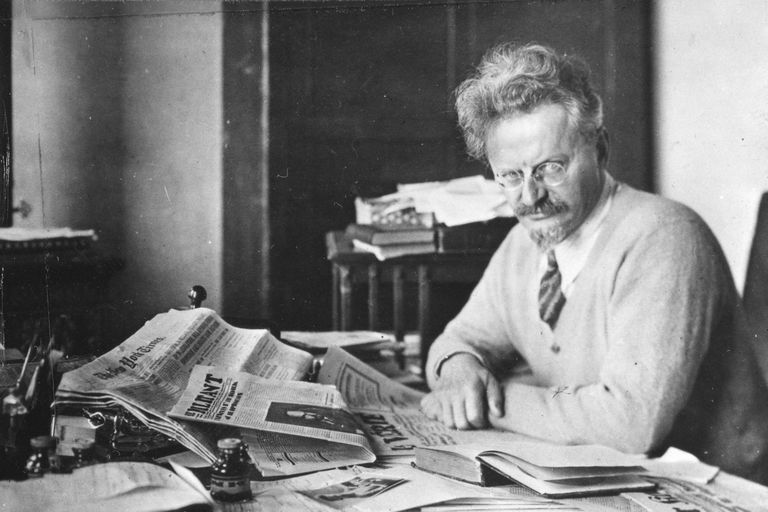Leon Trotsky at a desk with newspapers