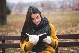 Young woman reading a book at the park in an autumn landscape.
