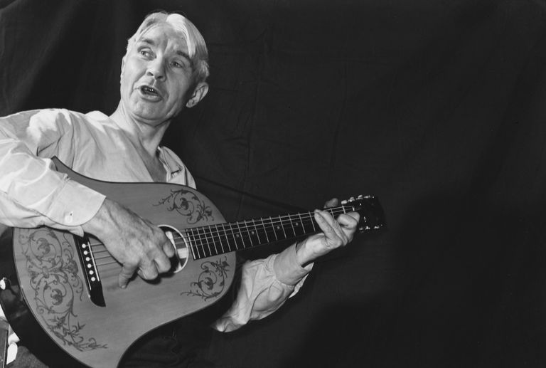photo of Carl Sandburg playing his guitar