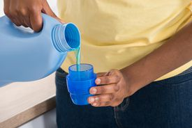 Female Hands Pouring Detergent In The Blue Bottle Cap