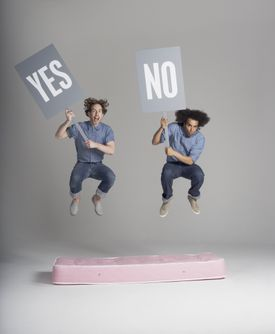 guys with signs bouncing on mattress