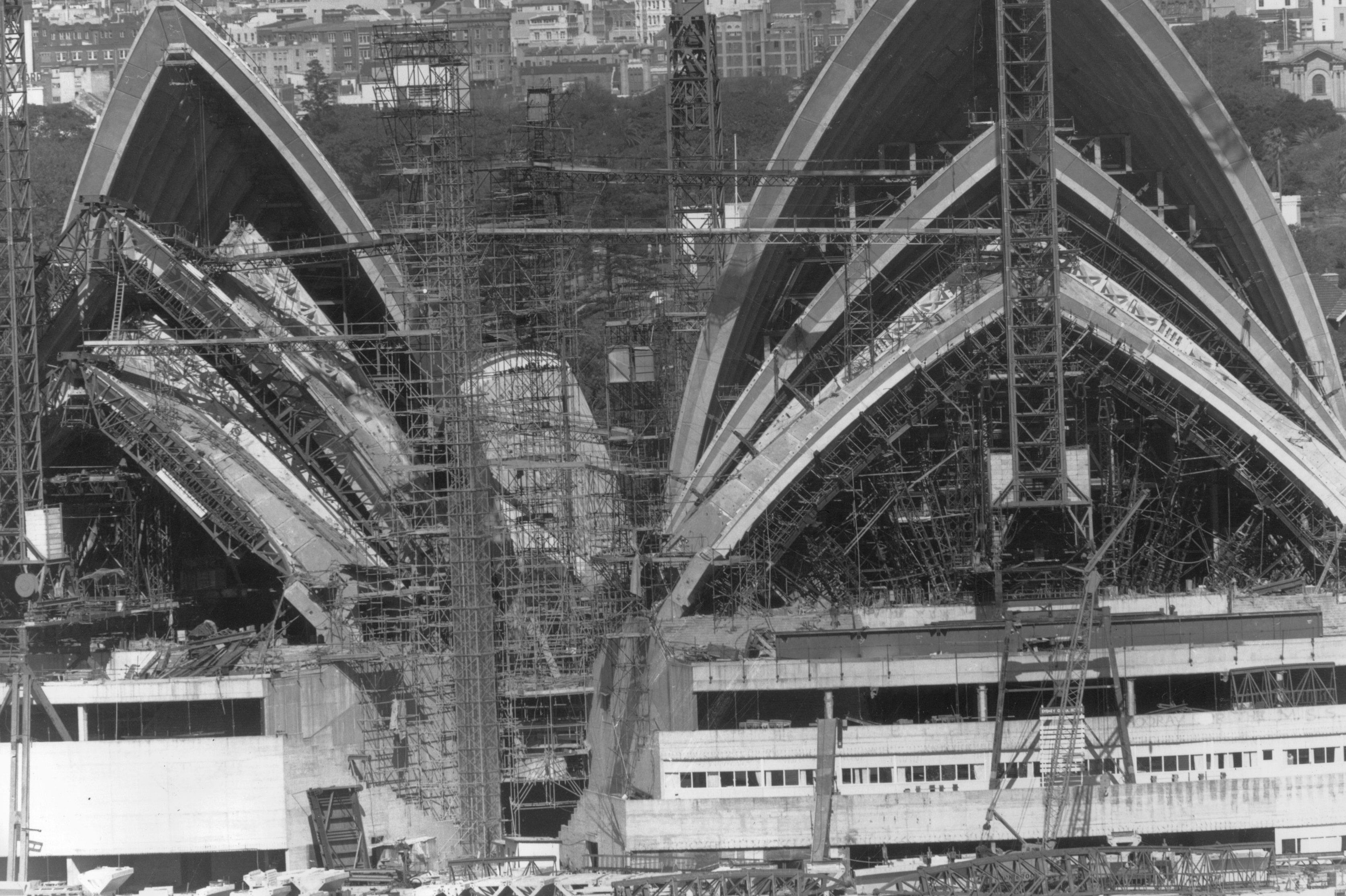 black and white photo of scaffolding and cranes surrounding triangular structures