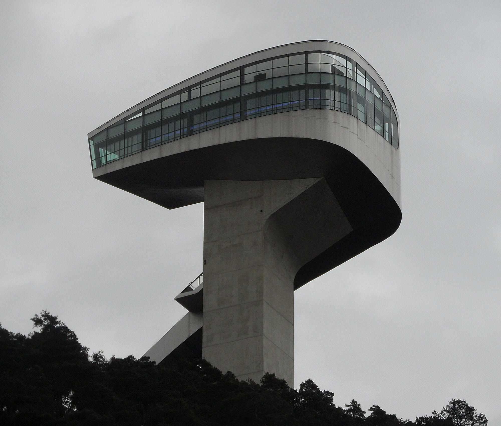 Innsbruck ski jump attached to glass-facade cafe atop a concrete pedestal.