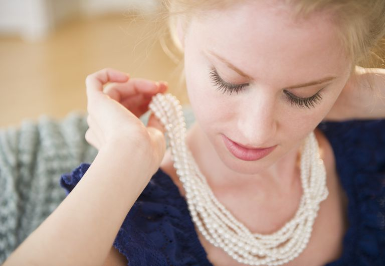 Woman putting on pearl necklace