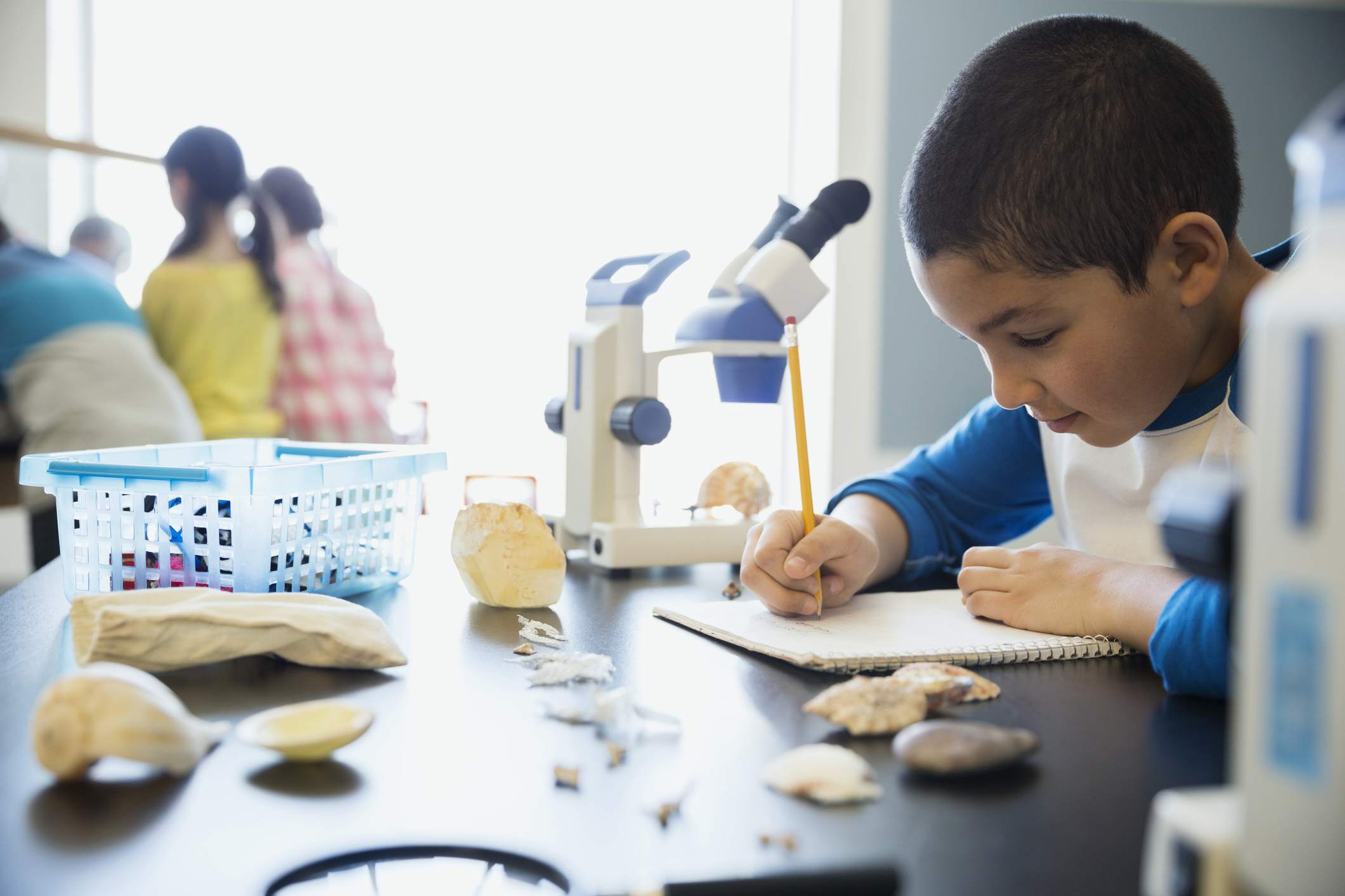 Schoolboy taking notes at microscope science laboratory classroom