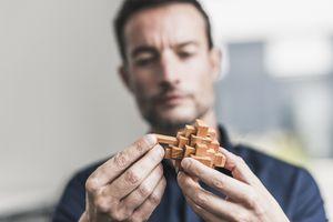 man solving wood puzzle