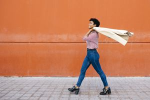 Businesswoman walking in front of red wall