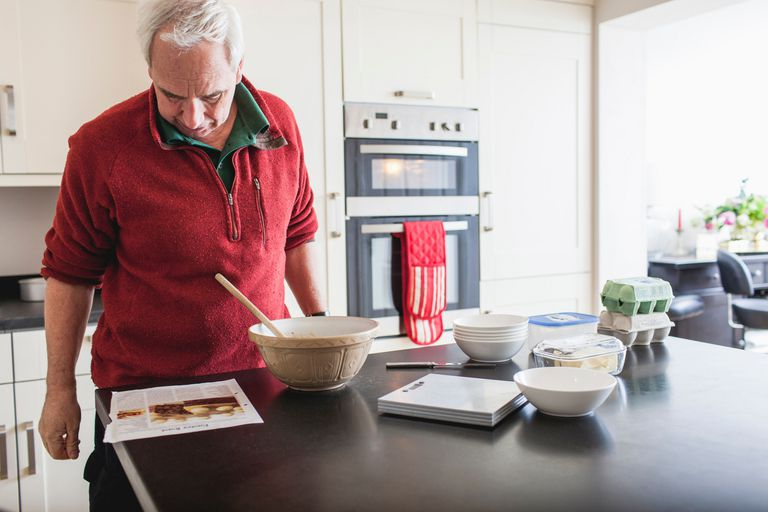 man studying recipe on kitchen counter