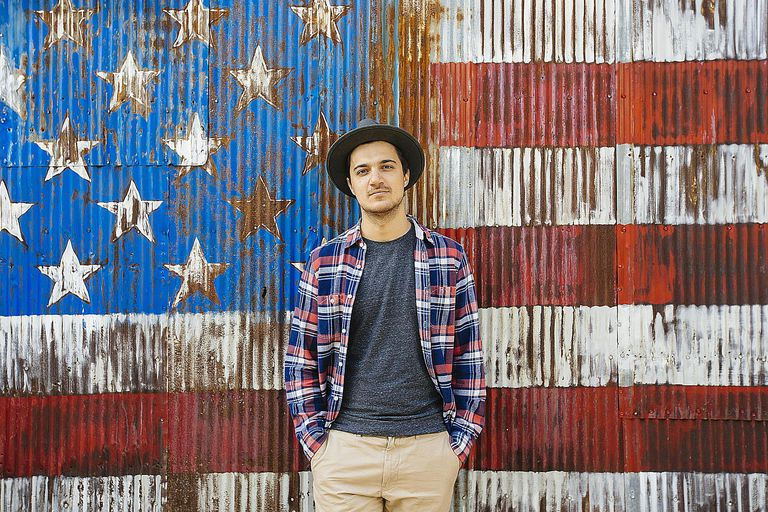 A young hipster man stands before an American flag. Find out what makes Americans stand out from others.