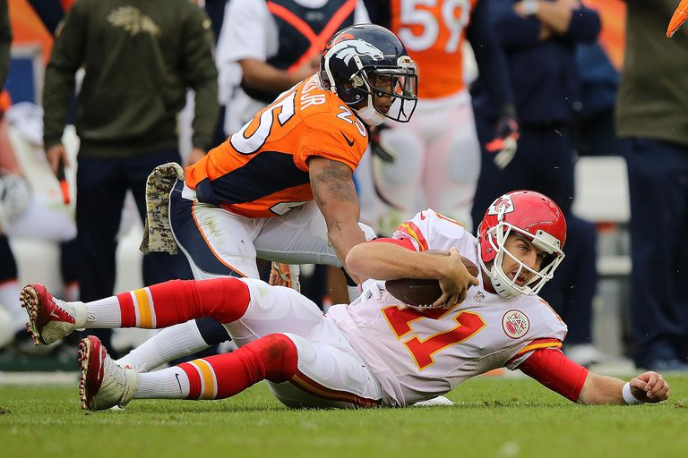 Quarterback Alex Smith #11 of the Kansas City Chiefs slides on the turf as he scrambles against Chris Harris #25 of the Denver Broncos